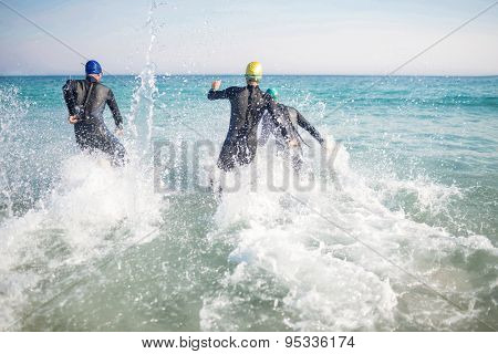Swimmers running in the ocean on a sunny day