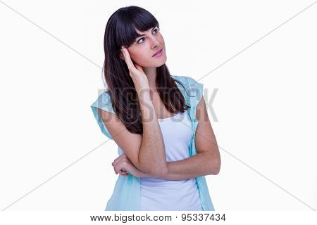 Pretty brunette with hand on head looking away on white background
