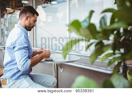 Distant view of businessman holding a cup of coffee outside the cafe