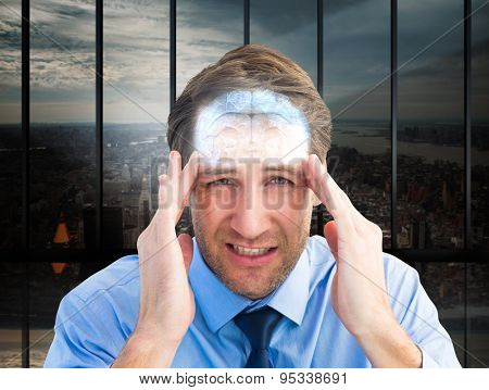 Young businessman with severe headache against room with large window looking on city