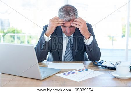 Worried businessman with head in hands in an office