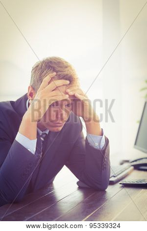 Irritated businessman looking his desk in the office