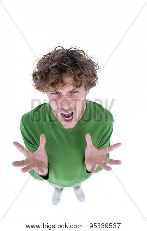 Angry casual man looking at camera on white background
