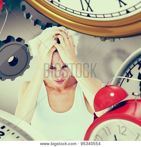 Sad blonde woman with head pain holding her head against grey vignette