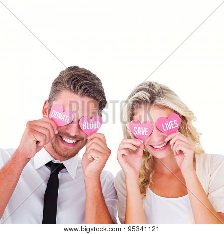 Attractive young couple holding pink hearts over eyes against donate blood save lives