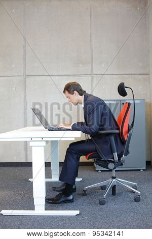 short-sighted business man bad sitting posture at laptop .