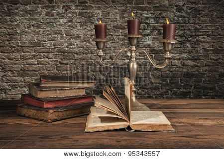 Old vintage books with candles in candlestick