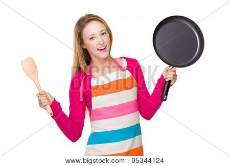 Young woman holding up with frying pan and wooden ladle