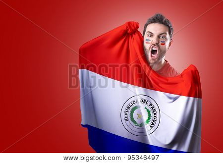 Fan holding the flag of Paraguay on red background