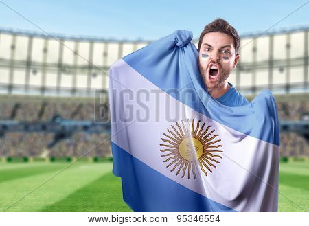 Fan holding the flag of Argentina in the stadium
