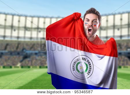 Fan holding the flag of Paraguay in the stadium