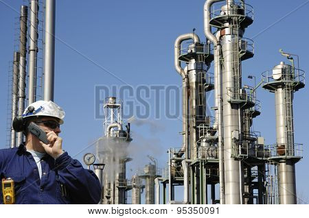 oil and gas worker with refinery towers in background