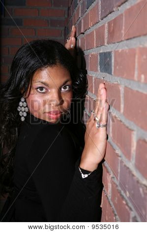 Pretty African American Woman Leaning Against Brick Wall