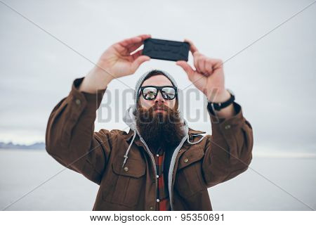 bearded hipster taking selfie in salt flats with retro tone