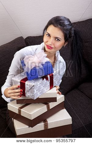 beautiful woman holds many holiday boxes with ribbon