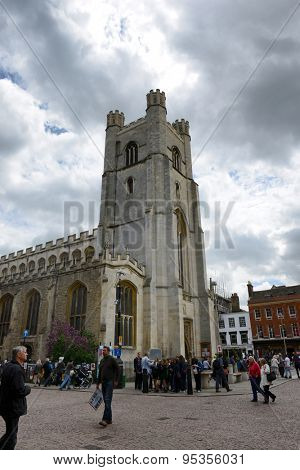 CAMBRIDGE, ENGLAND - MAY 13: Pedestrians Walking Past Church Tower Under Cloudy Sky, Kings College, University of Cambridge, England on May 13, 2015