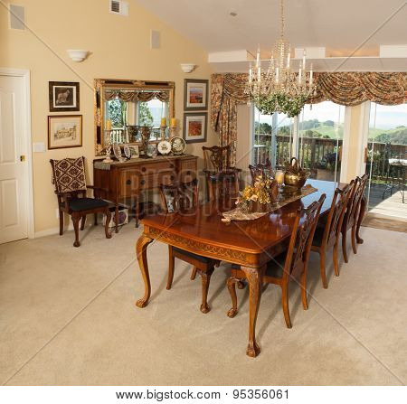 Large formal dining room with vaulted ceilings, chandelier, and a view from sliding doors