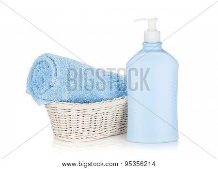 Shampoo bottle and blue towel. Isolated on white background