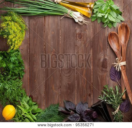 Fresh garden herbs and condiments over wooden table. Top view with copy space