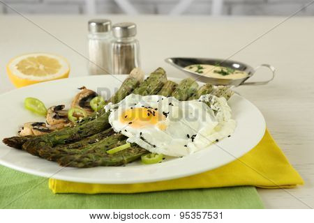 Roasted asparagus with poached egg on plate on table background