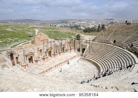 JERASH, JORDAN - MARCH 18, 2014: Tourists in the South theater in the ancient city of Jerash. Since 2004, Jerash Archaeological City is included in UNESCO Tentative List
