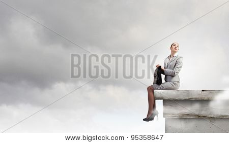 Fearless businesswoman with suitcase sitting on building top