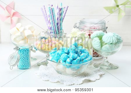 Sweet candies in glassware on table, closeup