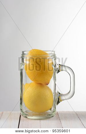 A still life with two lemons in a mason style jar with handle. The glass is on a rustic white wood table against a light to dark gray background with copy space.
