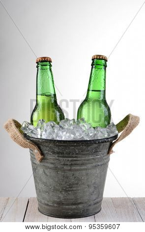 An old fashioned bucket with two beer bottles. Vertical format on a light to dark gray background with copy space.