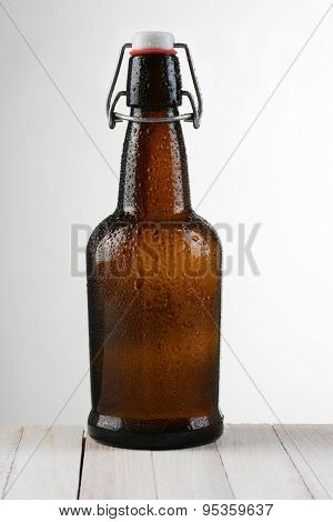 A swing top beer bottle against a light to dark background. The brown bottle is on a rustic whitewashed wood table. Vertical format with copy space.
