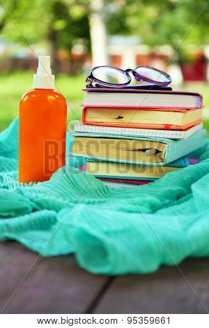 Books, glasses and sunscreen spray outdoors