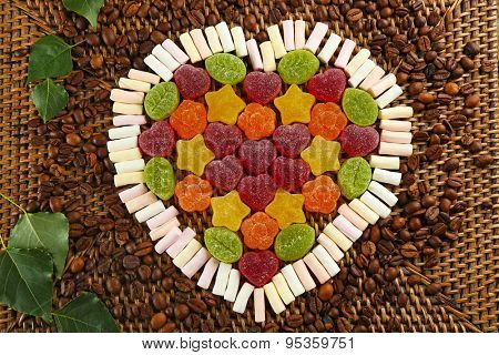 Gummy candies and marshmallow arranged in heart shape on table close up