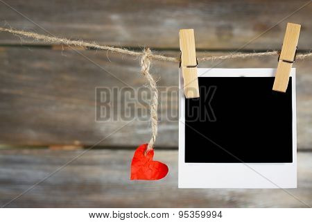 Bright heart and photo paper hanging on rope on wooden background
