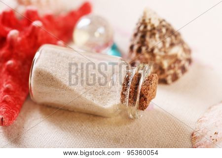 Collection of seashells and sand in glass bottle on textured surface, closeup