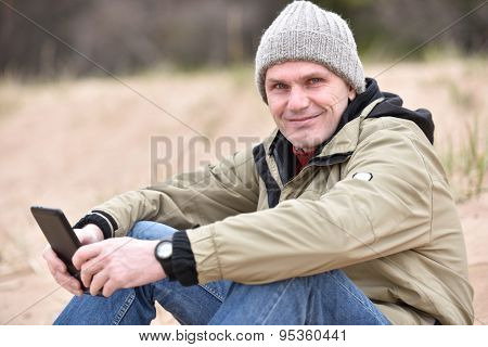 Mature man in jacket and knit hat holding the tablet outdoors