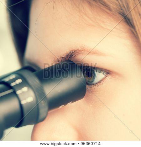 technician in the laboratory using a microscope