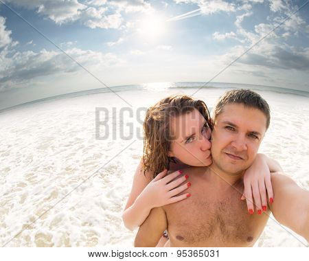 Young loving couple kissing making selfie against sunset seaside backdrop