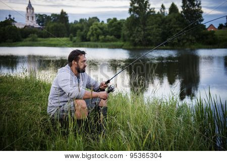 A fisherman with a fishing rod in his hands sitting on the river bank