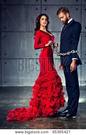Young happy woman in red dress holding man on heavy chain. Elegant evening clothing.