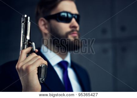 Danger man agent with gun and sunglasses. Focus on gun.