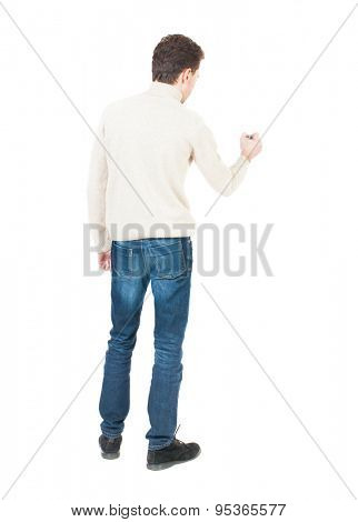 back view of writing man. Young man in jeans draws. Rear view people collection.  backside view of person. Isolated over white background.  The guy in white sweater draws felt-tip pen on the wall.