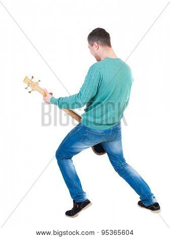 Back view young man with a guitar. Rock star with a musical instrument.  Rear view people collection.  backside view person.  Isolated over white background. Young bass player plays with enthusiasm.