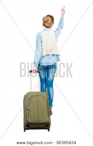 back view of walking  woman  with suitcase pointing. beautiful girl in motion.  backside view of person.  Girl in a blue shirt and sleeveless dragging a suitcase and shows thumb up.