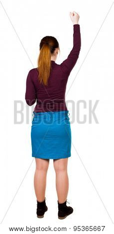 back view of dancing young beautiful  woman. girl  watching. Rear view people collection.    Isolated over white background. girl in a blue skirt and a burgundy sweater happily raised her hand up.