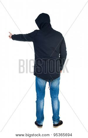 Back view of  pointing young men in parka. Young guy  gesture. Rear view people collection.    Isolated over white background. Man in warm jacket hood pulled on his head is and points to the left.