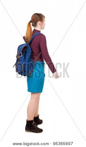 Back view of  woman with backpack looking up. Standing young girl. Rear view people collection. backside view person.  girl in blue skirt and burgundy sweater with a blue backpack goes to right.