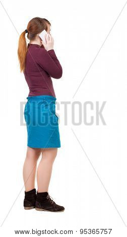 back view of standing young beautiful  woman and using a mobile phone. girl  watching. Rear view people collection. girl in a blue skirt and jacket of red and white talking cell phone.
