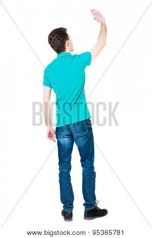 Back view of handsome man greeting waving from his hands. Standing young guy in jeans. Rear view people collection. The guy in a stylish T-shirt aquamarine waves up his hand in farewell.