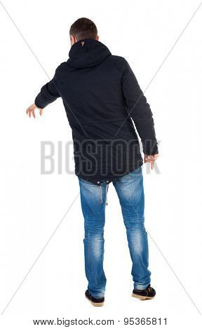 Back view of  pointing young men in parka. Young guy  gesture. Rear view people collection.  backside view person.  Isolated over white background. Man in warm jacket with his left hand points down.