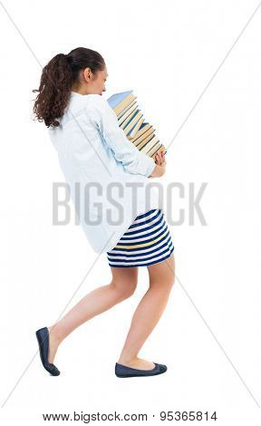 Girl comes with stack books.back view. Rear view people collection. backside view person. Isolated over white background. African-American woman in denim shirt comes hardly carrying heavy stack books.